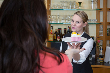 waitress gives piece of cake to client