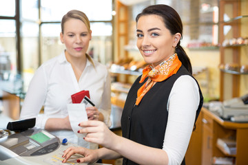 Client at shop paying at cash register