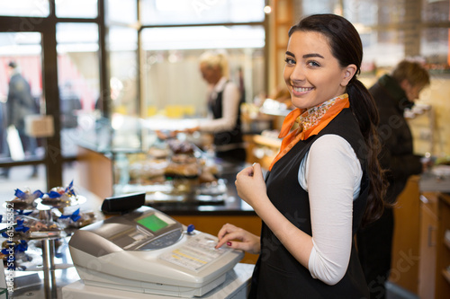 Salesperson at cash register - 61555352