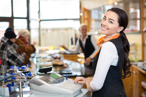 Salesperson at cash register - 61555360
