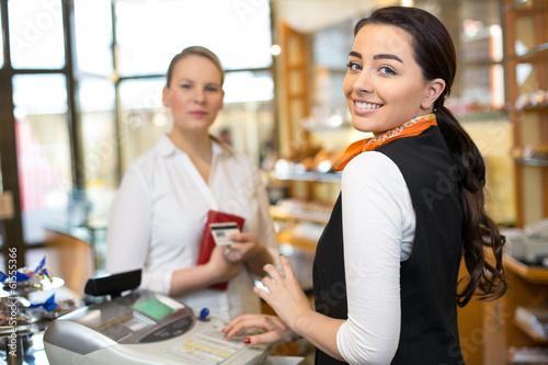Leinwanddruck Bild Client at shop paying at cash register