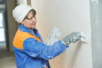 Plasterer at indoor wall work