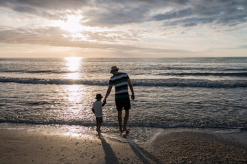 Father and son holding hands in front of the sunset at the beach