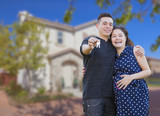 Hispanic Couple with House Keys In Front of New Home