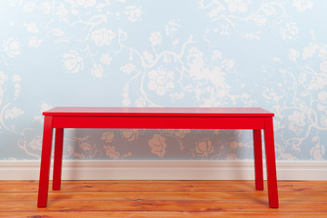 Room with blue vintage wall paper and red bench