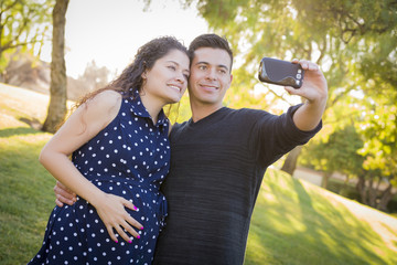 Pregnant Wife and Husband Taking Cell Phone Picture of Themselve