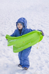 Boy carrying his sledge