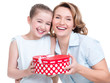happy  white mother and young daughter hold present