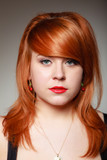 Portrait redhaired girl young woman with cherry earing on gray