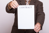 Businessman holding blank paper with sign contract
