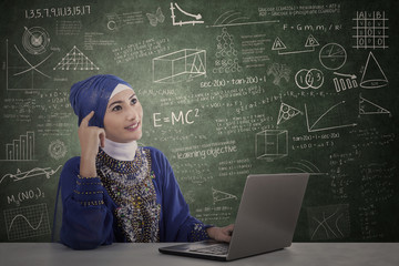 Asian muslim and laptop thinking at class
