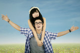Attractive couple piggyback outdoors