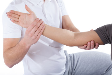 Physiotherapy doctor examining woman's elbow