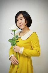 woman in yellow dress with a white roses