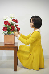 woman in yellow dress with a big bouquet of roses