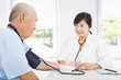 doctor measuring blood pressure of senior man at home