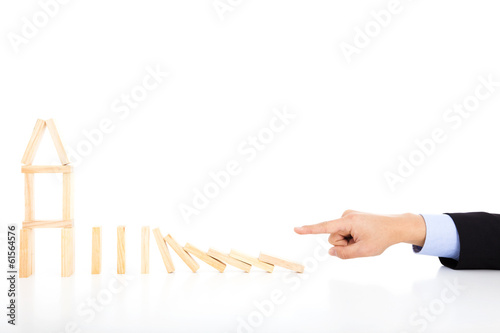 business person pushing dominoes to destroy house