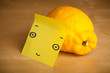 Post-it note with smiley face sticked on a lemon