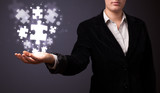 Puzzle pieces in the hand of a businesswoman