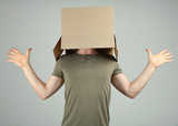 Man with cardboard box on his head on grey background