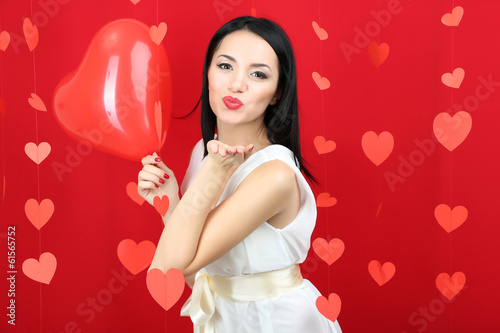 Attractive young woman with balloon on Valentine Day