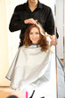 Young man hairdresser dyes hair girl in beauty salon