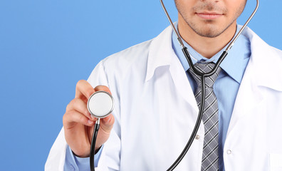 Male Doctor standing on blue background