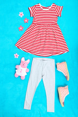 Beautiful clothes for little girl on blue background