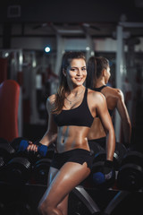beauty girl with dumbbells resting in the gym