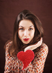 Portrait of beautiful young woman with red heart