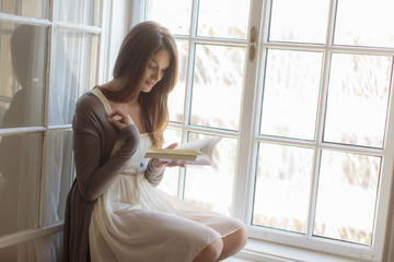 Young woman reading by the window