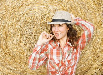 Portrait of beautiful young woman on the straw background
