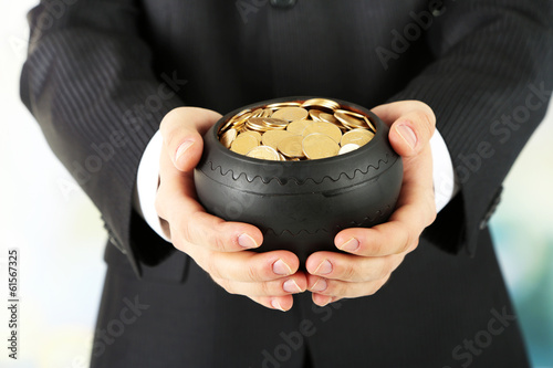 Ceramic pot with golden coins in male hands, on light