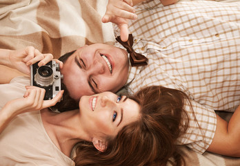 Beautiful vintage style smiling couple lying on the blanket