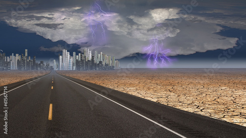 Stormy sky on desert road leading into city
