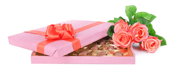 Delicious chocolates in box with flowers isolated on white