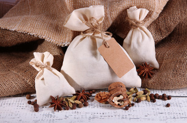Sacks full with spices, on wooden table, on sackcloth