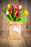 Tulips in the sack on wooden background