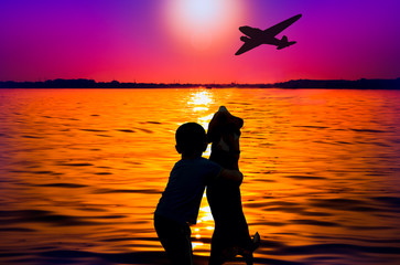 Silhouette of boy and dog at sunset watching aircraft