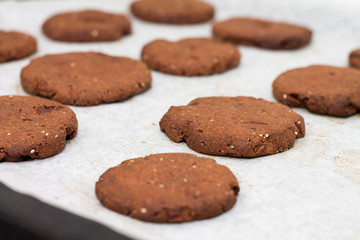 Tray of chocolate cacao chia seed cookies stacked on white parch