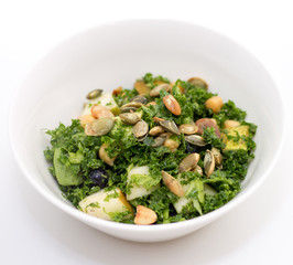 Kale salad in white bowl on white