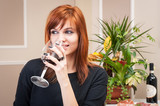 Young redhead woman drinking a glass of wine portrait inside a h