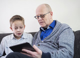 Young boy teaching grandfather tablet pc computer