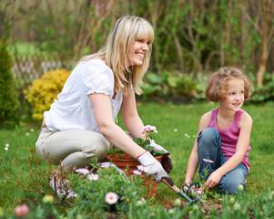 Frau und Kind machen Gartenarbeit im Frühling