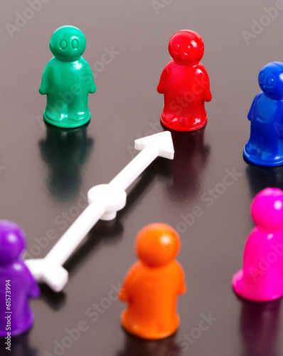 Group of toy people and white arrow pointing on the red one