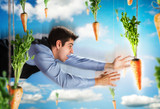 Businessman flying with carrots in blue sky