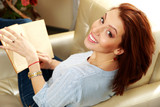 Smiling woman sitting on the sofa with book