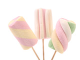 Three different colorful marshmallow on sticks.