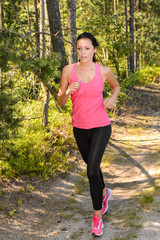 Athlete woman running through forest training