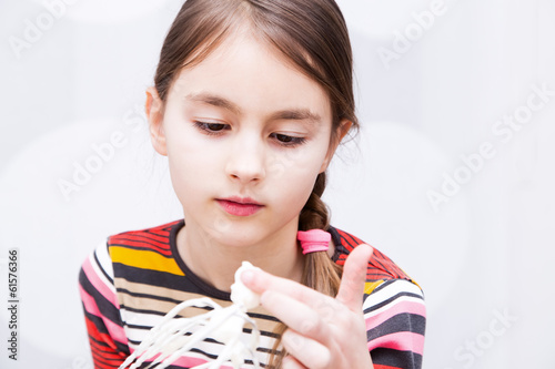 Little girl preparing food in bowl using wire whisk